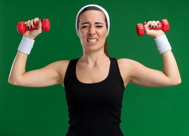 Giovane donna abbastanza sportiva tesa che indossa fascia e braccialetti che sollevano i manubri