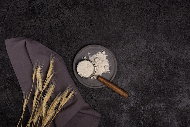 A strainer with a wooden handle with flour in a concrete plate on a black background. ears of wheat and a linen napkin. baking preparation