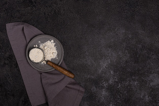 A strainer with a wooden handle with flour in a concrete plate on a black background