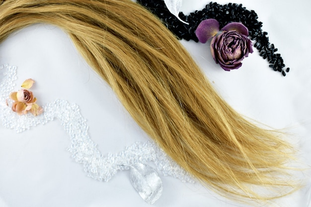 Strand of blond hair on a white background