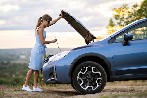 Молодая женщина-водитель, застрявшая возле разбитой машины с поднятым капотом, осматривает мотор своего автомобиля.