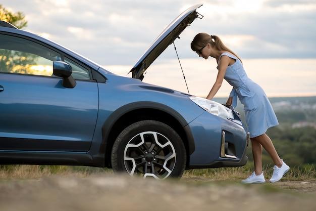 Застрявшая молодая женщина-водитель стоит возле разбитой машины с поднятым капотом Premium Фотографии