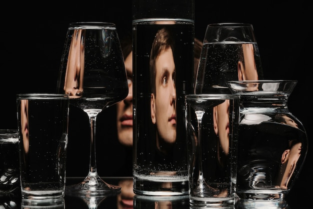 Strange abstract portrait of a man through the glass of the tank with water with the reflections and distortions Premium Photo