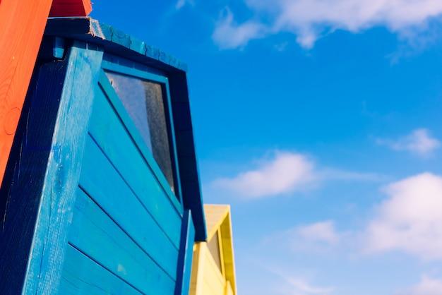 雲と青い空を背景にカラフルな木製三角板の奇妙なデザイン。