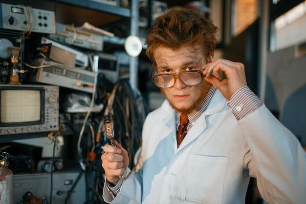 Странный инженер держит электрическую трубку в лаборатории.