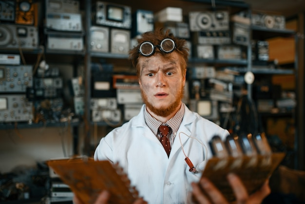 Странный инженер смотрит на электронные микросхемы в лаборатории