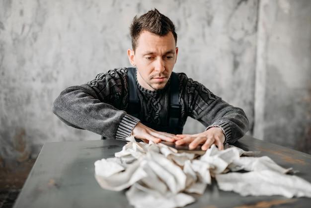 奇妙なフリークマンが本からシーツを引き裂く