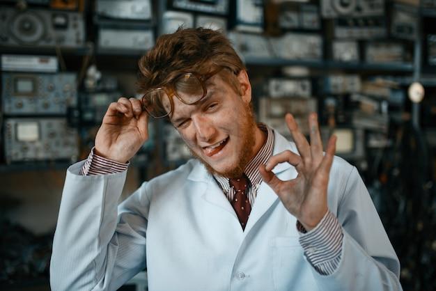 Странный ученый-мужчина показывает знак ок в лаборатории.
