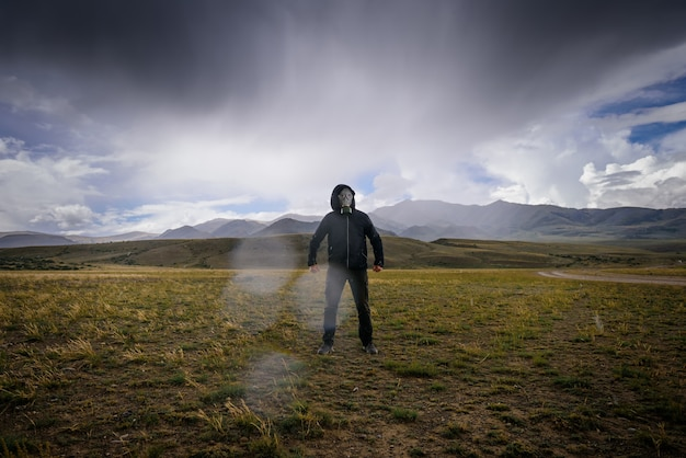 Strange man in black hood and gas mask on background of mountains, around smoke, fog and radioactive fallout.