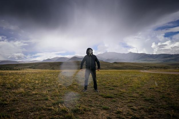 山の背景、煙、霧、放射性降下物の周りに黒いフードとガスマスクを身に着けた奇妙な男。