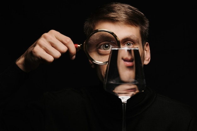 Strange portrait of a man looking through a magnifying glass and a glass of water on a dark background
