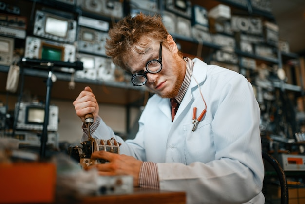 Strange scientist works with soldering iron in lab