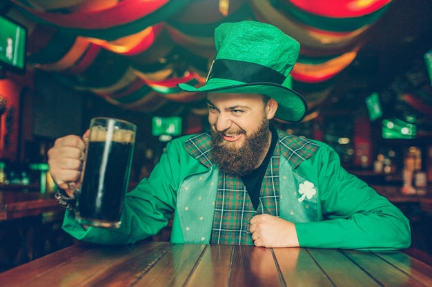 Strange young man wears green st. patrick's suit. he sit at table in pub and hold mug of dark beer. guy looks satisfied.