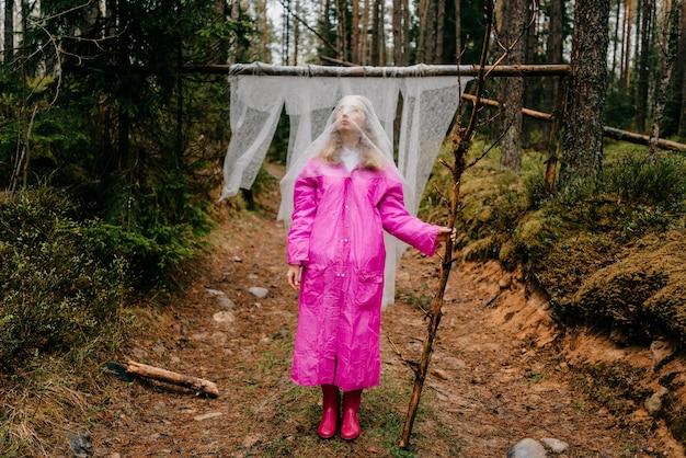 ピンクのレインコートを着た奇妙な若い女性が寒冷紗を覆い、森の中で棒を持ってポーズをとる