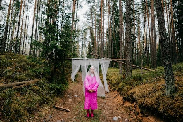 ピンクのレインコートを着た奇妙な若い女性が森の寒冷紗を覆ってポーズをとる