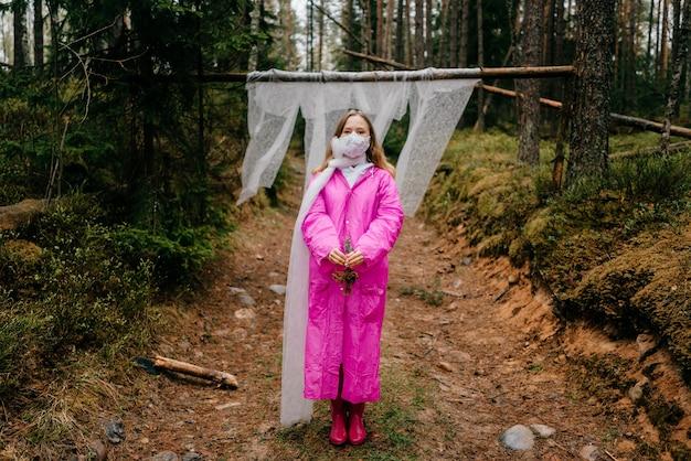 森の中でポーズをとるマスクとピンクのレインコートの奇妙な若い女性