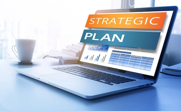 Текст стратегического плана на экране современного ноутбука с фоном диаграммы диаграммы