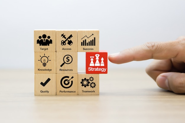 Strategy business concept icons on wooden blocks.