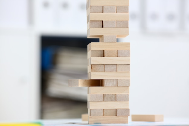 Strategy of jenga wooden blocks involved during break at work in office table gaming pile fun joy pastime concept