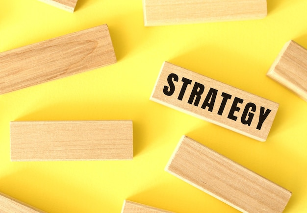 Strategy text written on a wooden blocks on a yellow background