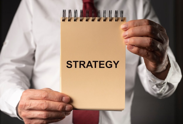 전략 단어, 사업가 손에 종이에 비문.