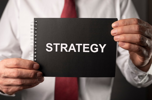 Strategy word, inscription on paper in businessman hands.