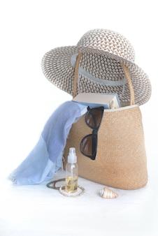 Соломенная сумка и шляпа с женскими аксессуарами, чтобы пойти на пляж на белом фоне