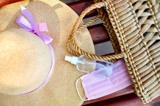 Соломенная сумка и шляпа с розовой защитной медицинской маской, гелем для рук, дезинфицирующим средством или антисептиком.