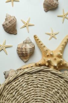 白い孤立した背景の上のわらのバッグと貝殻