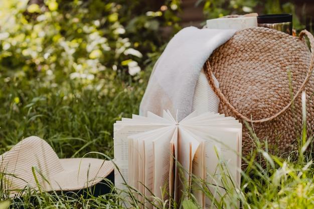 Соломенная сумка, книга, шляпа в солнечный летний день