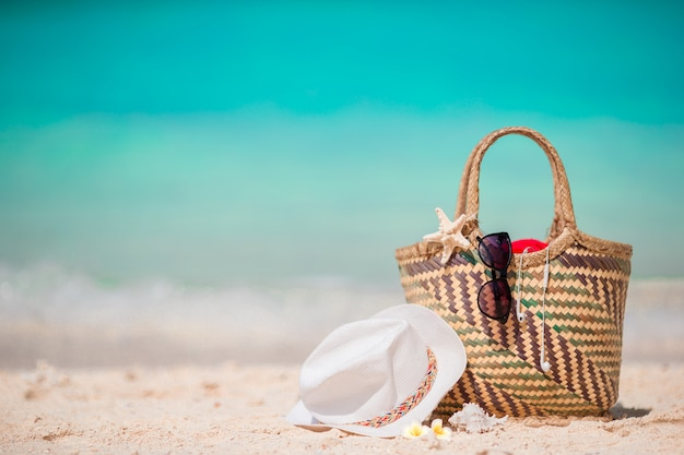 Straw bag, fist star, headphones, hat and sunglasses on white beach