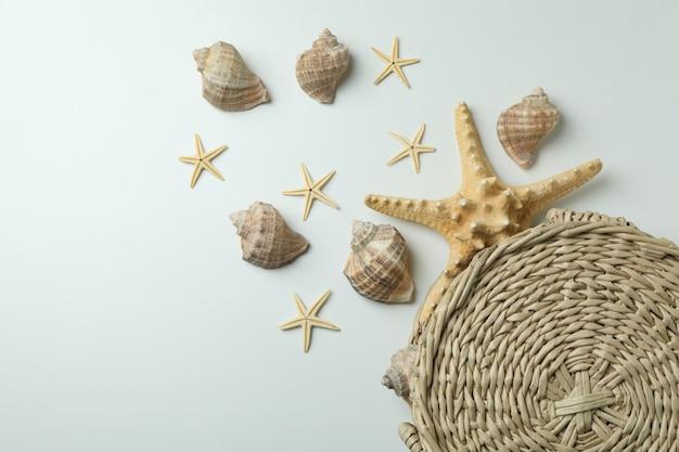 Straw bag and seashells on white isolated background