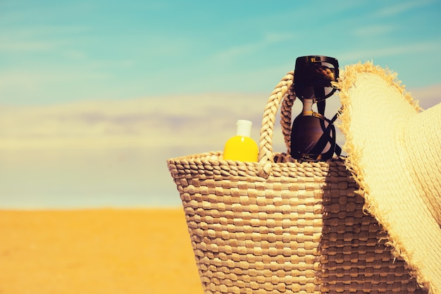 Straw bag, sunglasses, a bottle of sunscreen lotion  a hat with dead sea beach  .