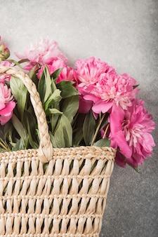 회색 바탕에 분홍색 모란 꽃과 함께 밀 짚 가방.