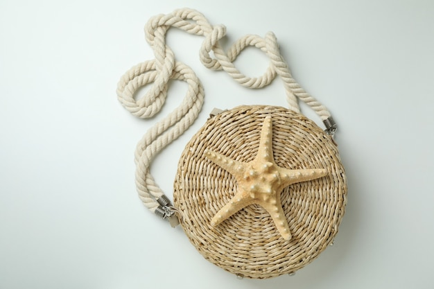 Straw bag with starfish on white isolated background