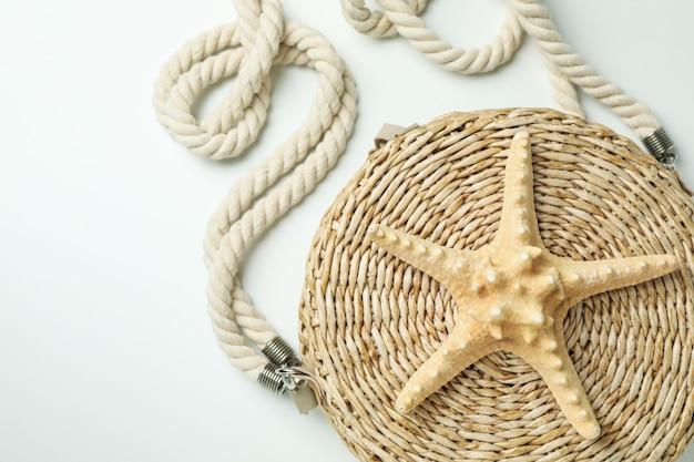 Straw bag with starfish on white
