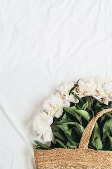 白い背景に白い牡丹の花が付いたストロー バッグ。フラットレイ、トップビュー