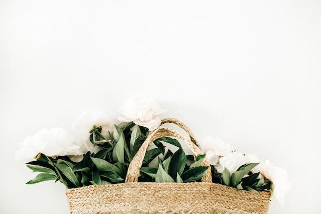 Соломенная сумка с белыми цветами пиона на белой поверхности