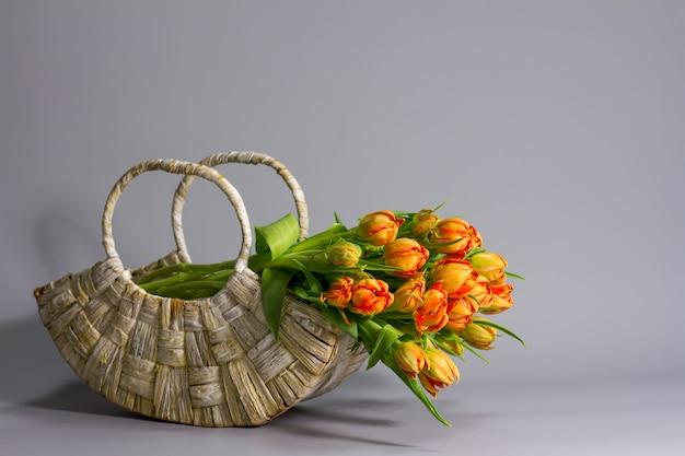 Straw basket with bouquet of fresh orange tulips