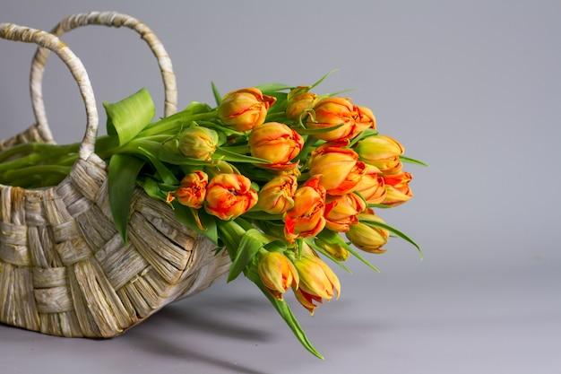 新鮮なオレンジのチューリップ、挨拶やギフトのコンセプトの花束とストローバスケット