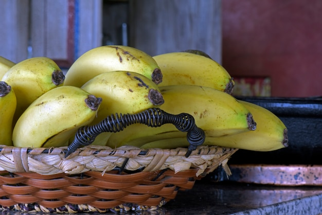 Straw basket with bunch of ripe bananas
