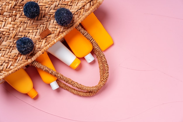 Straw beach bag full of sunblock products, top view