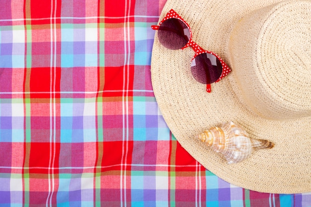 Straw beach hat, sun glasses and seashell on checkered towel