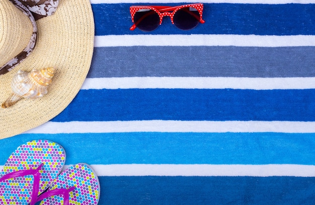 Straw beach woman's hat sun glasses top view seashell flip flops with space for text.