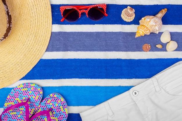 Straw beach woman's hat sun glasses top view seashell shorts flip flops background