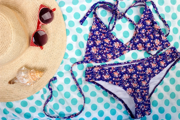Straw beach woman's hat sun glasses top view seashell women's swimsuit with space for text.