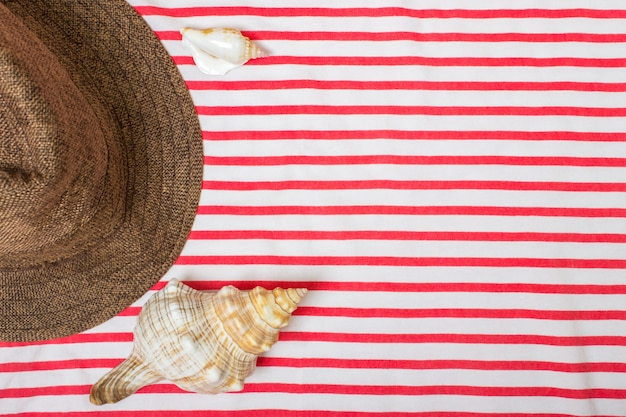 Straw beach woman's hat sun top view seashell with space for text.