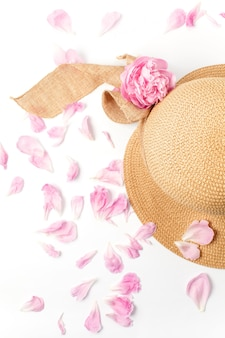 Straw braided hat, pink peony flowers and petals on white, top view.