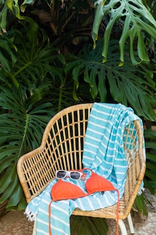 Disposizione di sedia e costume da bagno in paglia