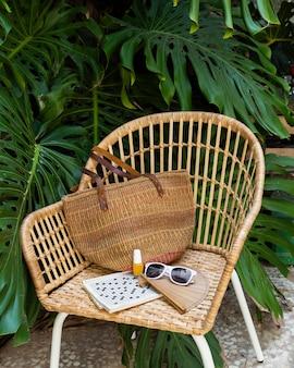 Disposizione di sedia in paglia e articoli da viaggio